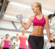Smiling woman lifting steel dumbbell Royalty Free Stock Image