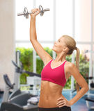 Smiling woman lifting steel dumbbell at gym Stock Images