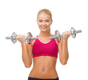 Smiling woman lifting steel dumbbells Stock Image