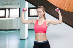 Smiling woman lifting weights in the gym Royalty Free Stock Image