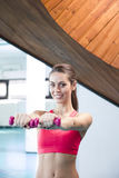 Smiling woman lifting weights in the gym Stock Photos
