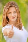 Smiling woman lifts thumb Royalty Free Stock Image
