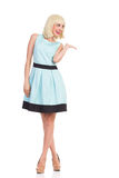 Smiling woman in light blue color dress presenting product Stock Photo
