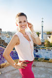 Smiling woman listening audioguide in Park Guell, Barcelona royalty free stock images