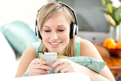 Smiling woman listening music at home Stock Photo