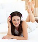 Smiling woman listening music lying on bed Royalty Free Stock Photo