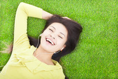 Smiling  woman listening music and lying Royalty Free Stock Photos