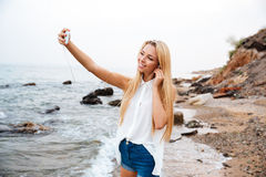 Smiling woman listening music and making selfie on the beach. Young smiling beautiful woman listening music and making selfie while standing on the rocky beach Royalty Free Stock Photo