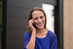 Smiling woman listening to a call on her mobile Stock Image
