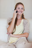 Smiling woman listening to caller on her cellphone Stock Photography