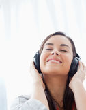 A smiling woman listening to her headphones Stock Image