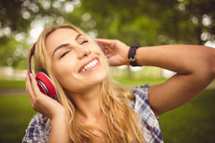 Smiling woman listening to music with eyes closed at park Royalty Free Stock Photography