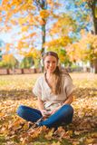 Smiling woman listening to music in a fall park Royalty Free Stock Image