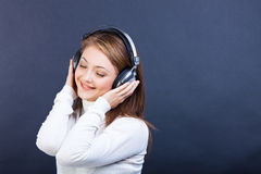 Smiling woman listening to music in headphones. Studio shot of beautiful young smiling woman listening to music in headphones Royalty Free Stock Images