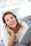 Smiling woman listening to music with headphones Royalty Free Stock Photography