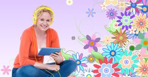 Smiling woman listening to music on headphones using tablet PC against floral background Stock Images
