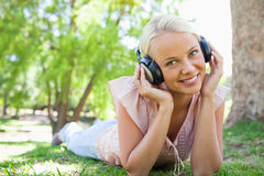 Smiling woman listening to music while lying Royalty Free Stock Images