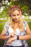 Smiling woman listening to music and using smartwatch while sitting on grass Stock Image