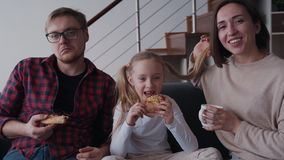 Smiling woman, little daughter and man eating pizza and cuddle. Family of three happy person sitting on comfort couch in cozy flat with modern interior stock footage