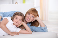 Smiling woman and little girl on a sofa Stock Photos