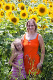 Smiling woman and little girl on sunflowers field Royalty Free Stock Image