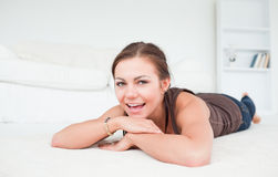 Smiling woman liying on a carpet royalty free stock photo