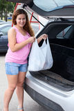 Smiling woman loading shopping bag in trunk of her pov Stock Photo