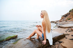 Smiling woman with long blonde hair sitting on the beach Stock Photography