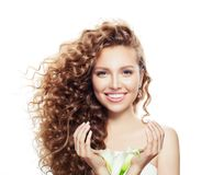Smiling woman with long curly hair isolated on white. Beautiful model with clear skin and flowers in hands portrait stock image