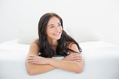 Smiling woman looking away in bed Royalty Free Stock Photos
