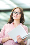 Smiling woman looking away while holding book outdoors Stock Photo