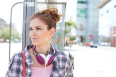 Smiling woman looking away while waiting at bus stop Royalty Free Stock Photography