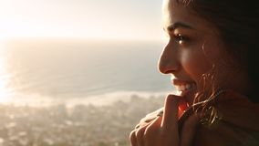Smiling woman looking at beautiful view. Close up of african female face. Woman standing outdoors and looking at the view with smile on her face stock photography
