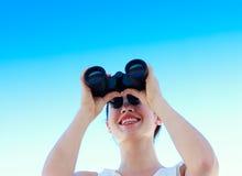 Smiling woman looking through binoculars Royalty Free Stock Photos