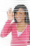 Smiling woman looking through blinds Royalty Free Stock Images