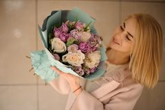 Smiling woman looking at the bouquet of tender bright violet and peach color flowers. Wrapped in the blue paper stock photo