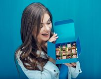 Smiling woman looking in box with chocolate candy. Portrait on blue Royalty Free Stock Image
