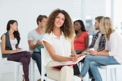 Smiling woman looking at camera while colleagues are talking behind her. Smiling women looking at camera while colleagues are talking behind her in creative Stock Images
