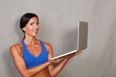 Smiling woman looking at camera and holding laptop Stock Photos