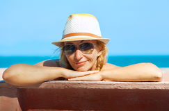 A smiling woman looking at the camera on the sea background Stock Photo