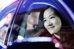 Smiling woman looking through car window at the city nightlife, reflected lights Stock Photos