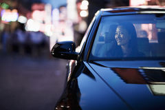 Smiling woman looking through car window at the city nightlife Stock Images