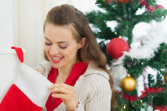 Smiling woman looking into Christmas socks Stock Photography