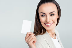 Smiling woman looking at credit card in hand stock photography