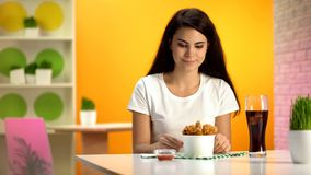 Smiling woman looking at disposable bowl with crispy fried chicken, fast food royalty free stock photos