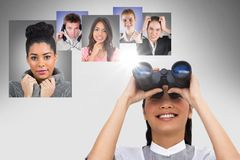 Smiling woman looking at flying portraits of business people with binocular royalty free stock photography