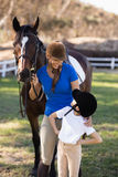 Smiling woman looking at girl with arms akimbo. Smiling women looking at girl with arms akimbo while standing by horse at paddock Royalty Free Stock Image