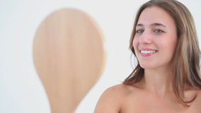 Smiling woman looking at a hand mirror stock footage