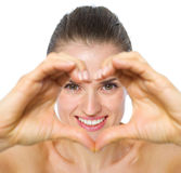Smiling woman looking through heart shaped hands Royalty Free Stock Photography