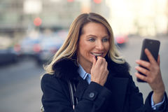 Smiling woman looking into her phone on street Stock Photography